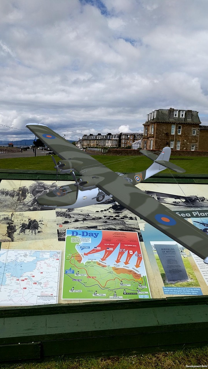 Model PBY Catalina flying boat flies above panel installation of Largs D-Day Connection