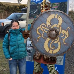 Knight and tourist standing by totem sign, Haylie Brae, Largs