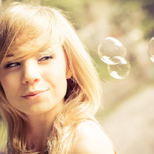 beautiful blonde girl watching bubbles floating by